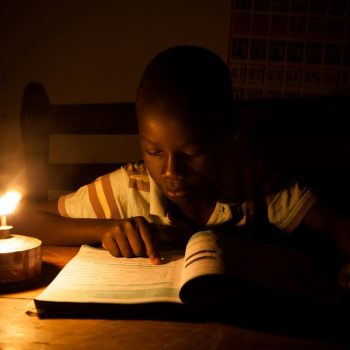 African boy reading by kerosene light